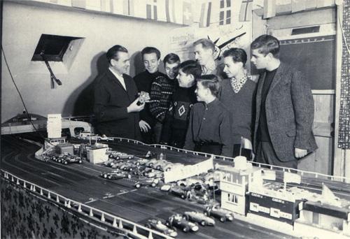 Acht Personen stehen an einer Carrerabahn